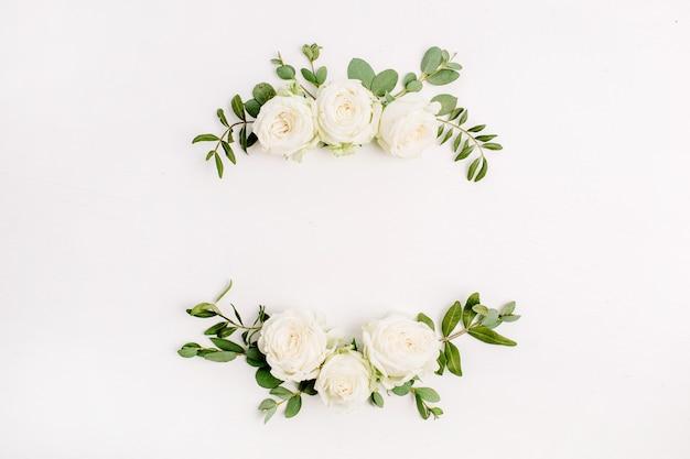 Corona di cornice floreale fatta di boccioli di fiori di rosa bianca su sfondo bianco. disposizione piatta, vista dall'alto
