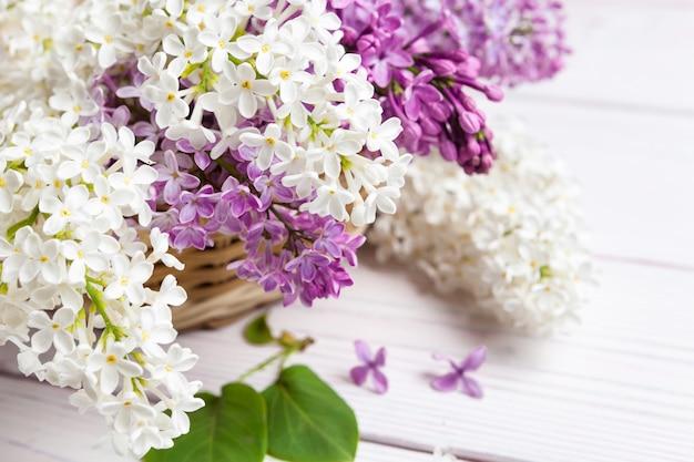 Rami e petali lilla del modello floreale sul telaio di legno del fondo