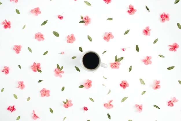 Motivo floreale fatto di fiori di ortensie rosa, tazza di caffè, foglie verdi, rami su bianco