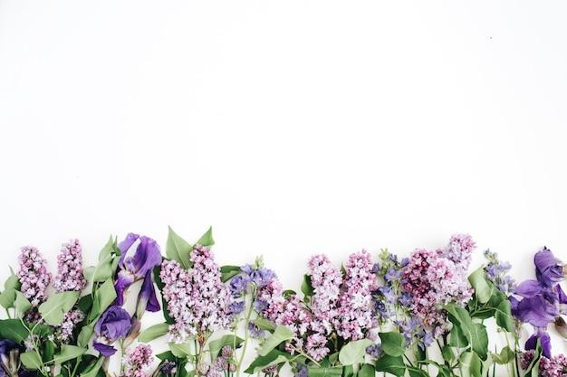 Motivo floreale con fiore lilla, fiore di iris viola, foglie verdi, rami su bianco