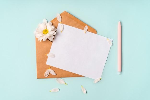Composizione romantica floreale. fiori di camomilla bianchi e busta su sfondo blu