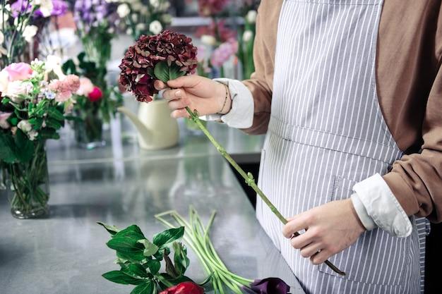 Negozio di fiori. fiorista competente in piedi al suo posto di lavoro mentre compone ikebana