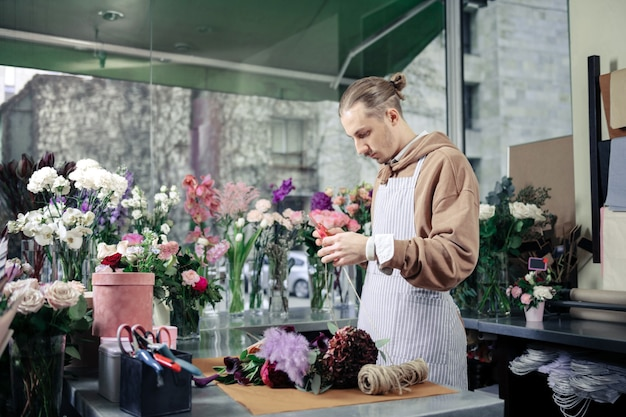 Negozio di fiori. fiorista professionista immerso nei pensieri durante la creazione del risultato