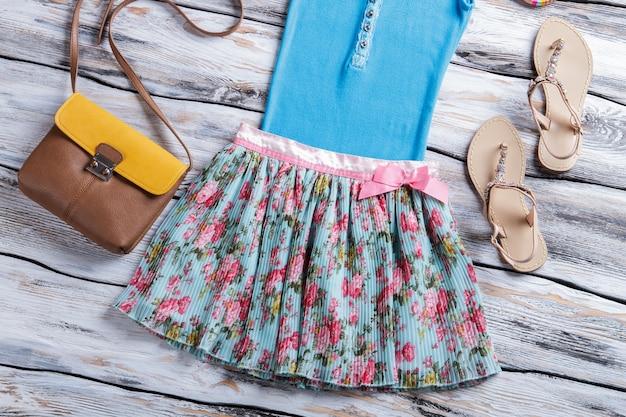Gonna floreale e top blu. top con sandali e borsetta. vestiti nuovi di zecca in mostra. trova il tuo stile.
