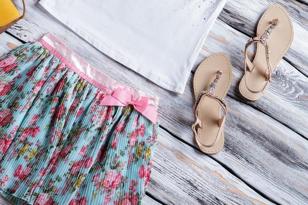 Gonna floreale con fiocco rosa. sandali beige e gonna estiva. abbigliamento da ragazza nuovo di zecca. scegli la tua taglia.