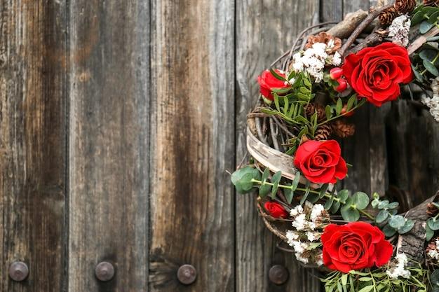 Ghirlanda floreale con bellissimi fiori sullo sfondo della parete in legno