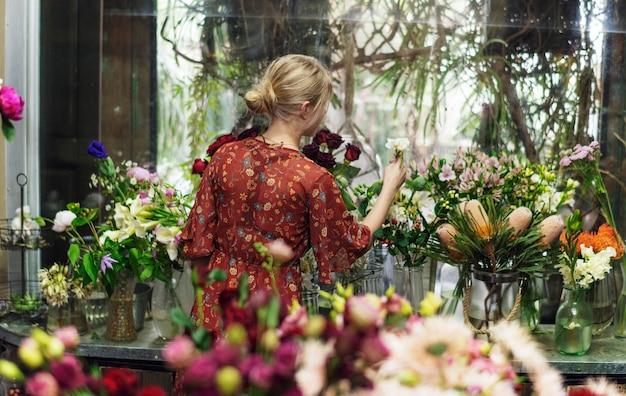 Fiorista che sistema lisianthus nel suo negozio