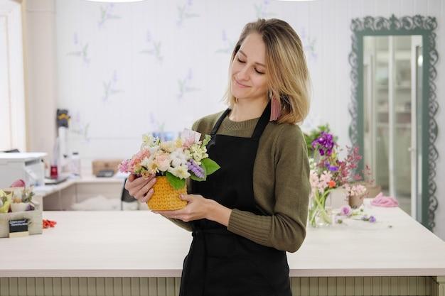 Fiorista in un grembiule nero detiene un bouquet floreale