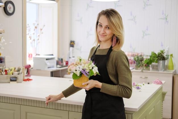 Fiorista con un grembiule nero tiene tra le mani una composizione floreale