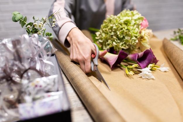 Il fiorista taglia la carta da imballaggio per un mazzo di fiori.