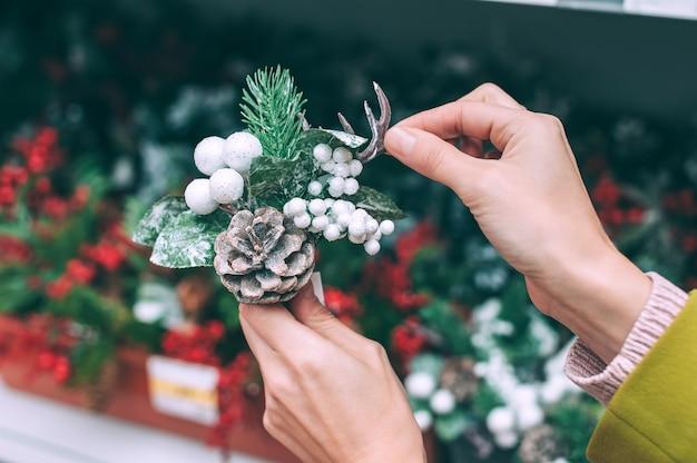 Una fioraia tiene in mano un ramo di abete con bacche e coni per la decorazione di natale e capodanno.