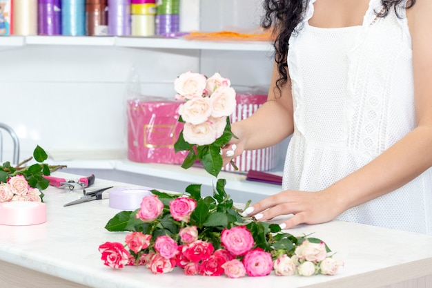 Ragazza del fiorista che lavora in un negozio di fiori. morbide sfumature di fiori freschi di primavera impara a padroneggiare il fiorista che condivide le sue abilità mostrando come disporre i fiori in un bouquet perfetto e bellissimo