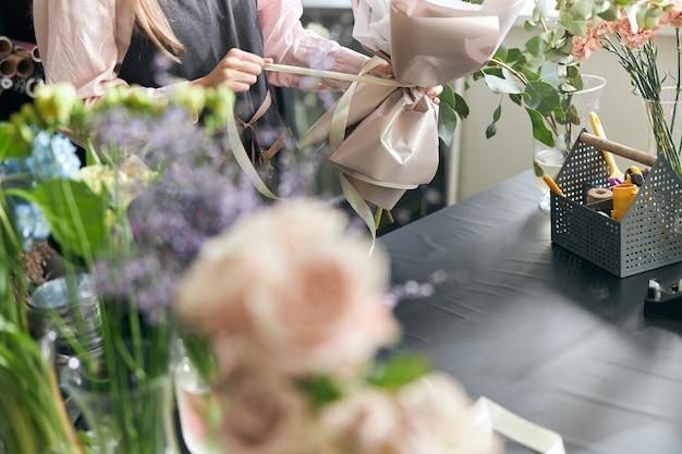 Fiorista che tiene il nastro decorativo mentre fa il bouquet nel negozio di fiori. bella composizione floreale. dettaglio. avvicinamento.
