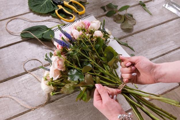 Il fiorista fa un mazzo di fiori di rosa. il decoratore lavora in una serra con un bouquet rosa. laboratorio floristico, abilità, arredamento, concetto di piccola impresa