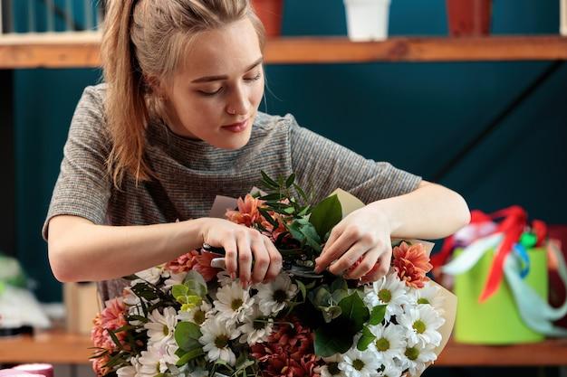 Il fiorista fa un bouquet. una giovane ragazza adulta taglia i fiori in un bouquet di crisantemi multicolori con un potatore.