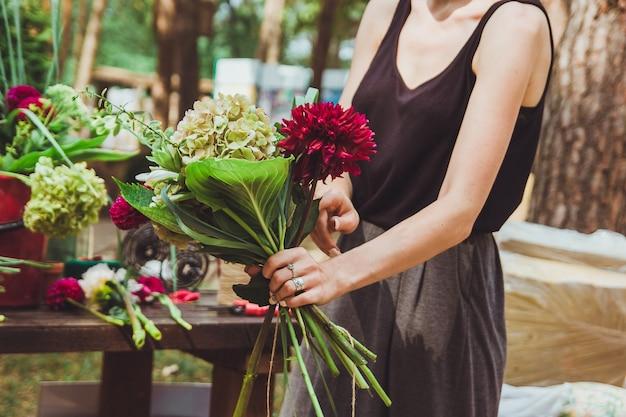 Fiorista rendendo il bouquet moderno di moda di fiori diversi all'aperto