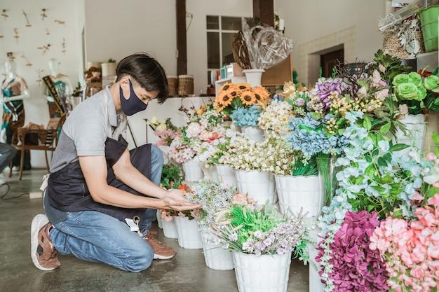 Uomo fiorista utilizzando la maschera per il viso controllando un bouquet di fiori nel negozio di fiori