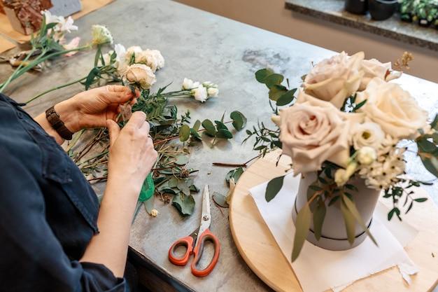 Il fiorista prepara fiori e piante per creare un bouquet insolito per le vacanze.