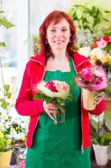 Fiorista che vende fiori e mazzi di fiori in negozio