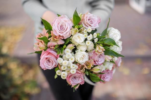 Fioraio alla luce del giorno. una donna tiene un bellissimo mazzo di fiori