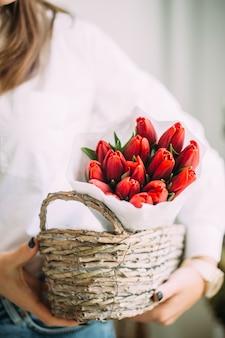 Donna fiorista che tiene un cesto con tulipani rossi in carta bianca.