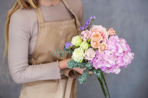Fiorista al lavoro. le mani femminili raccolgono un romantico bouquet di rose.