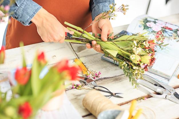 Fioraio al lavoro: le mani femminili della donna che fanno moda moderna bouquet di fiori diversi