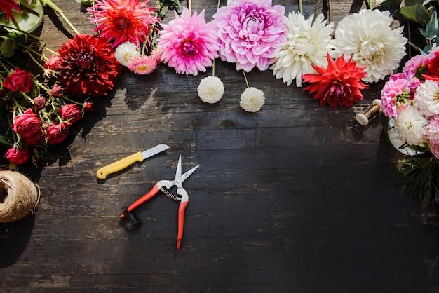 La tavola di lavoro del fiorista con gli strumenti su fondo di legno scuro. copia spazio