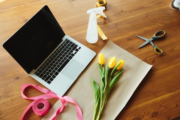 Fioraio al tavolo di lavoro con tulipani e narcisi, nastri e carta di copertura contro laptop