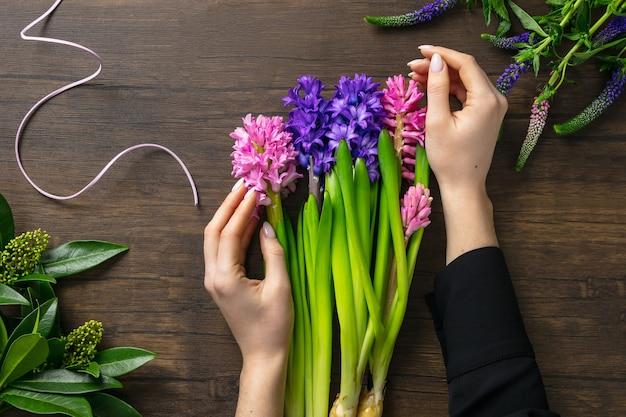 Fiorista al lavoro donna che fa moda moderna bouquet di fiori diversi su una superficie di legno