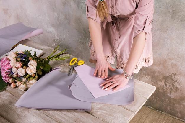 Fiorista avvolgente bouquet di fiori di rosa. il decoratore lavora in una serra con un bouquet rosa. laboratorio floristico, abilità, arredamento, concetto di piccola impresa