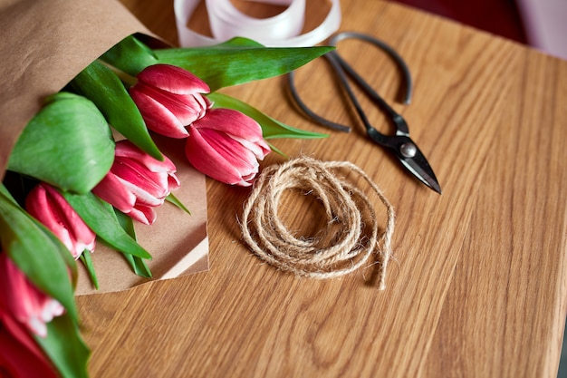 Posto di lavoro floristico con carta artigianale, spago disposizione di un mazzo di tulipani rossi su un tavolo di legno