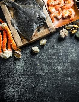 Passera pianuzza pesce sul vassoio con granchi, gamberetti e ostriche scuro sul tavolo rustico
