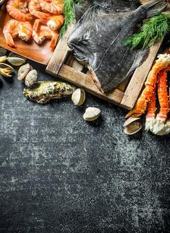 Pesce passera sul vassoio con granchio, gamberetti e ostriche. su rustico scuro
