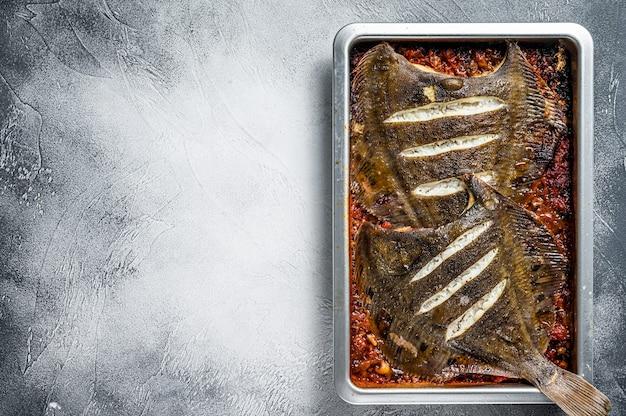 Pesce piatto passera di mare arrosto in salsa di pomodoro nella teglia. vista dall'alto.
