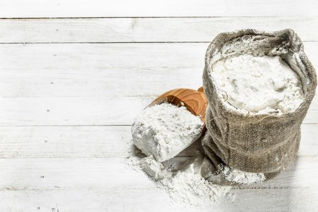 Farina in sacchetto con pala. su un tavolo di legno bianco.