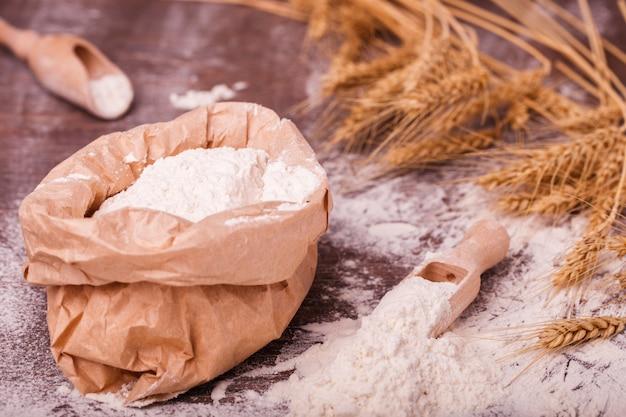 Farina in sacchetto e cucchiaio di legno
