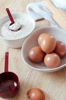 Ciotola per farina con misurino rosso e ciotola con le uova