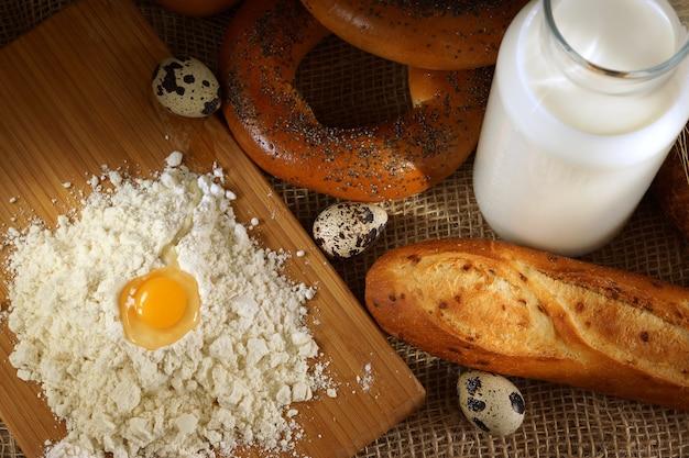 Farina e uovo su una tavola in una panetteria, accanto a una baguette pronta e una bottiglia di latte