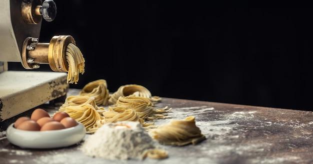 Farina, uova e una macchina per la pasta che produce fettuccine fresche italiane con uno sfondo scuro.