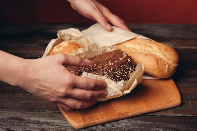 Prodotti di farina al forno pagnotta di pane su tavola di legno e sfondo rosso in background