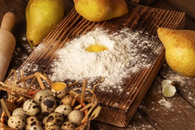 Farina, uova di quaglia, pere su tavola di legno