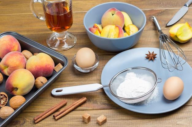 Farina, setaccio e uovo sul piatto. pesche e noci in teglia. pesche affettate in ciotola. bicchiere di tè e bastoncini di cannella sul tavolo.