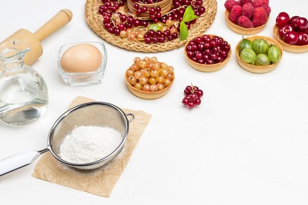 Farina al setaccio, uovo e mattarello, bottiglia d'acqua. tartellette ai frutti di bosco. ribes rosso sul piatto di vimini. copia spazio. sfondo bianco. vista dall'alto
