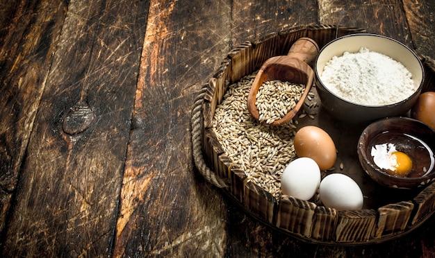Farina con chicchi di grano su un vecchio vassoio. su uno sfondo di legno.