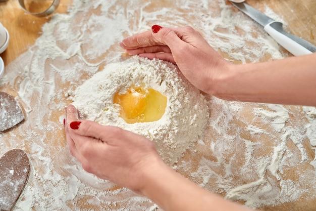 Farina, tuorlo e piatto bianco giacevano sul tagliere di legno.