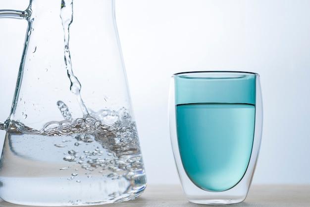 Il flusso d'acqua sta versando nel bicchiere verde su sfondo bianco.