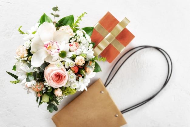 Fiorisca il mazzo con il contenitore e la borsa di regalo su fondo bianco disposizione piana, concetto floreale di san valentino o di festa della mamma di vista superiore