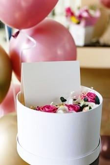 Fioriera con carta bianca, composizione di fiori di rose. mazzo del regalo e cartolina d'auguri dentro con spazio vuoto per la vostra progettazione, logo. palloncini festivi.
