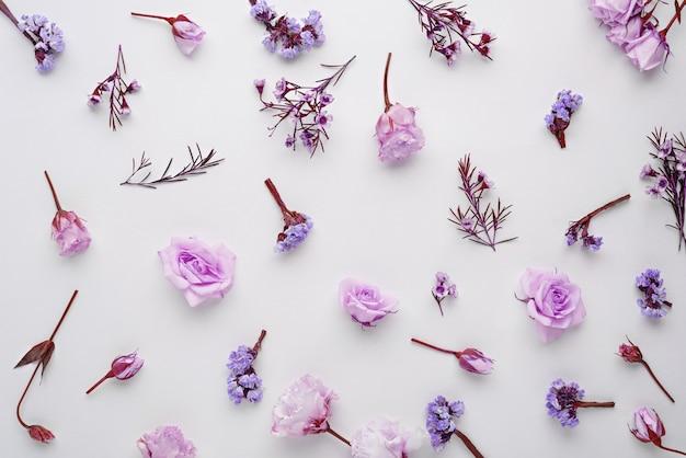 Composizione di fiori, rose rosa, eustoma, limonium su sfondo bianco, piatto laico, spazio copia, vista dall'alto, concetto di primavera